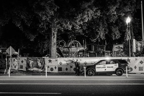 Greyscale Photo of Two Policemen Standing Infront of a Parked Police Car
