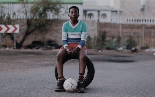 Boy Sitting on Vehicle Tire
