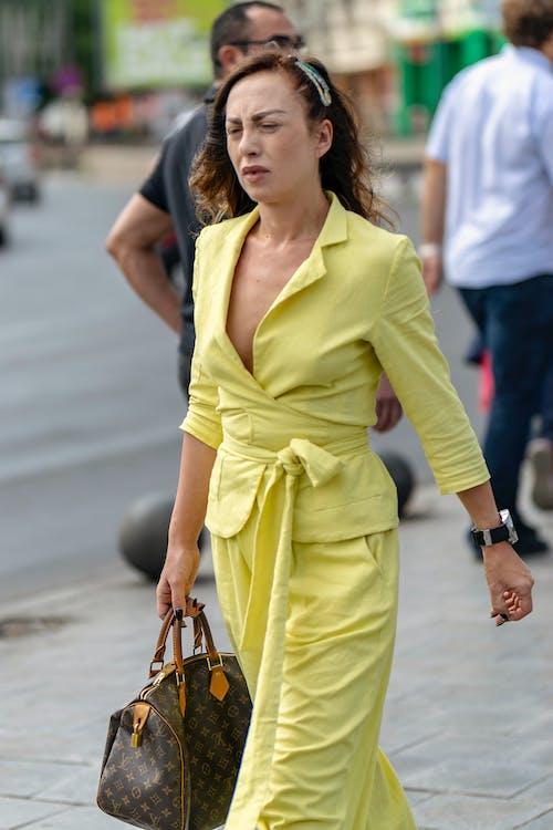 Darmowe zdjęcie z galerii z kobieta w żółtym chodzenia po ulicy