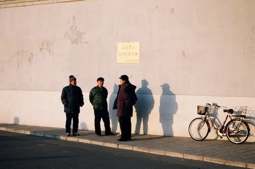 Three Men Standing Near Parked Bicycle
