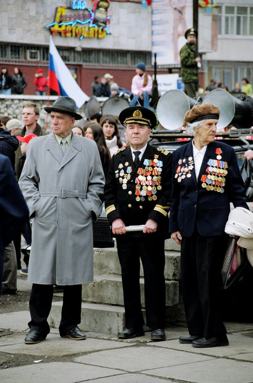 Veterans of Great Patriotic War in formal suits with medals of honor with man in outerwear resting on street during holiday of Victory Day in city