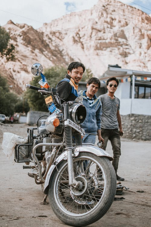 Three Men Standing Near Black Motorcycle Beside House