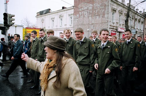 Woman Standing in Front of Military Personnel on Road