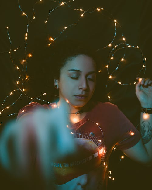 Woman Wearing Red Shirt Covered in String Lights