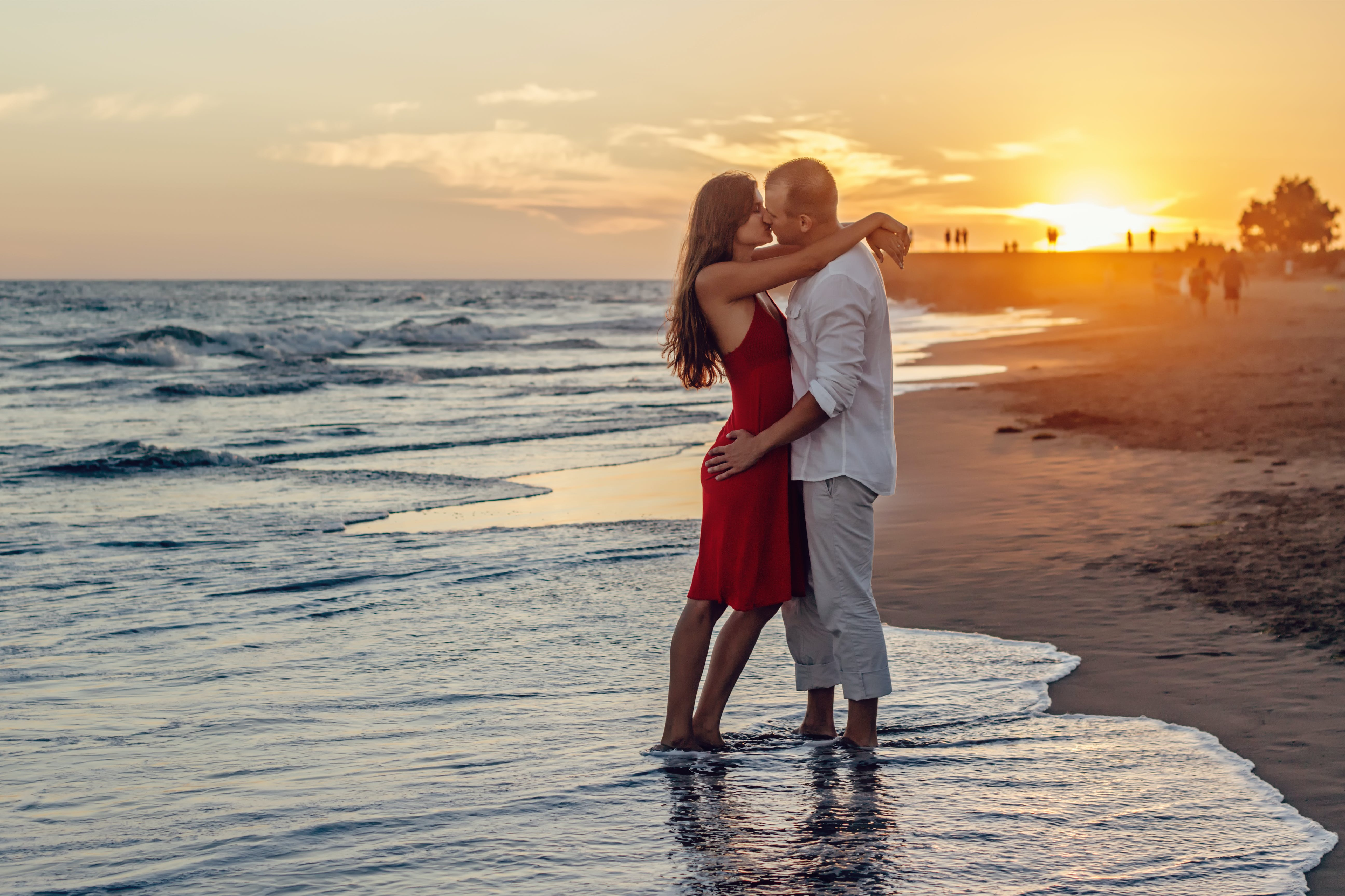 Couple Kissing on Beach during Golden Hour