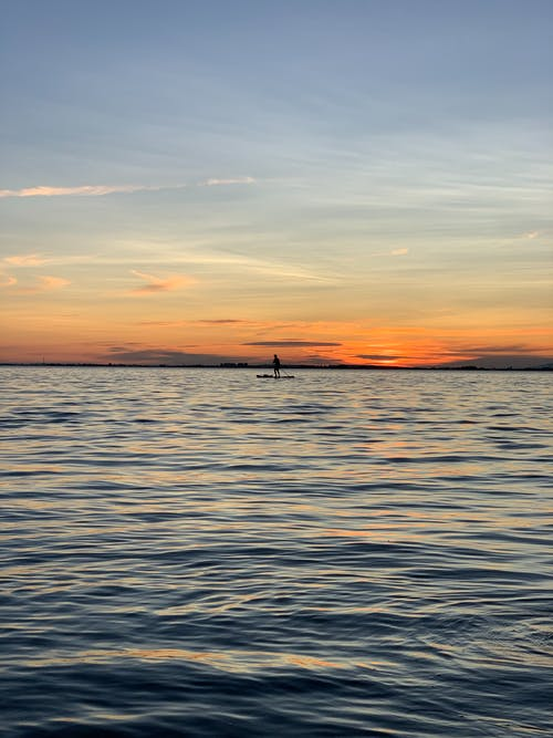 Person Standing on Paddle Board Under Orange Skies