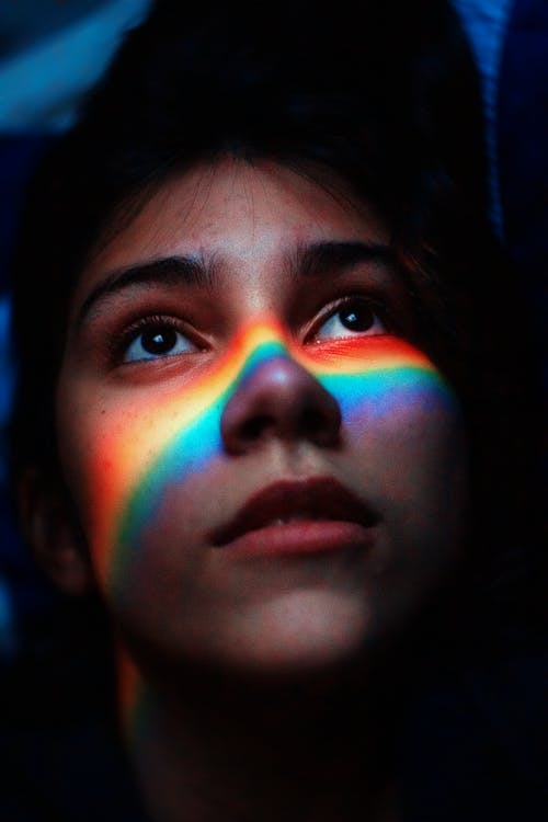 Woman With Rainbow Light Reflecting Her Face