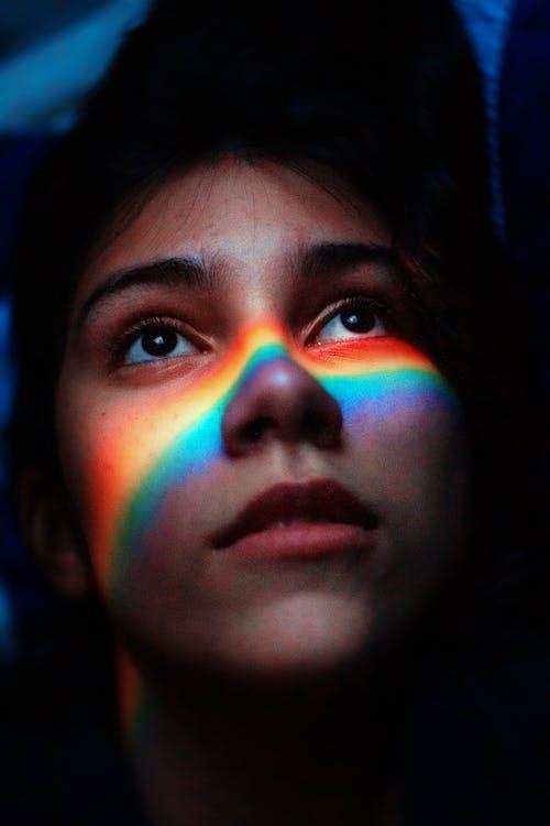 Mujer Con Luz De Arco Iris Reflejando Su Rostro