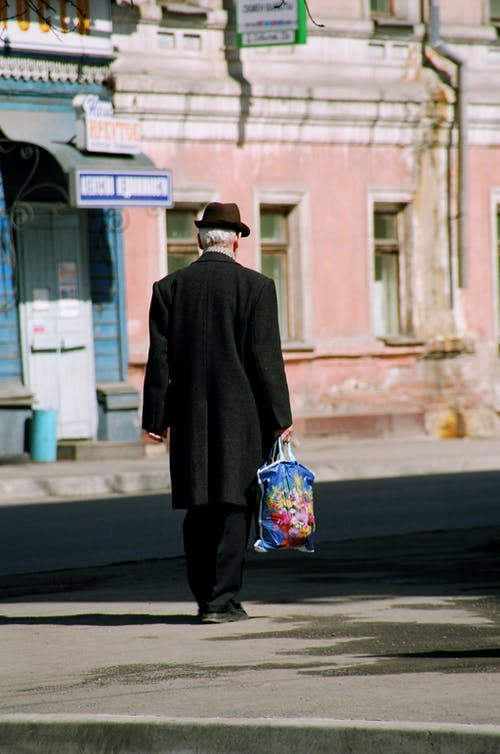 Back view of anonymous elderly man in dark outerwear and hat carrying packet and walking on street against old shabby buildings in city