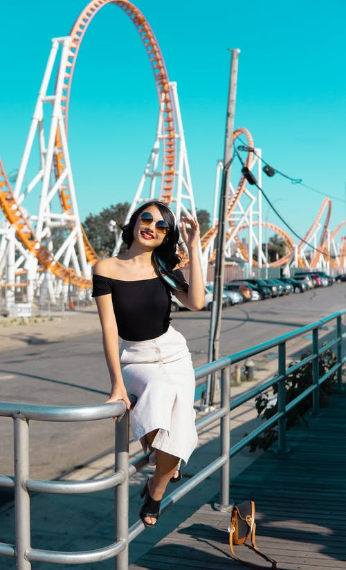 Woman in Black Off-shoulder Top, White Skirt, and Black High-heeled Mules Sitting on Silver Balustrade With Roller Coaster Background