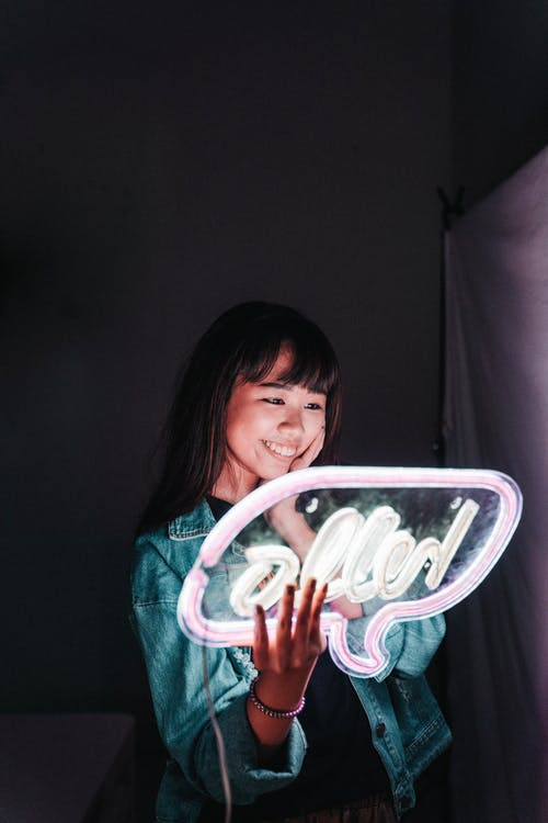 Woman Holding Hello Neon Signage