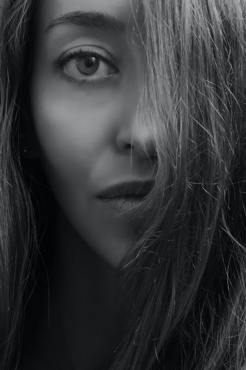 Grayscale Photo of Woman Covering Half Face With Hairs