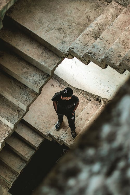 Man Wearing Black Crew-neck T-shirt Standing on Concrete Stairs