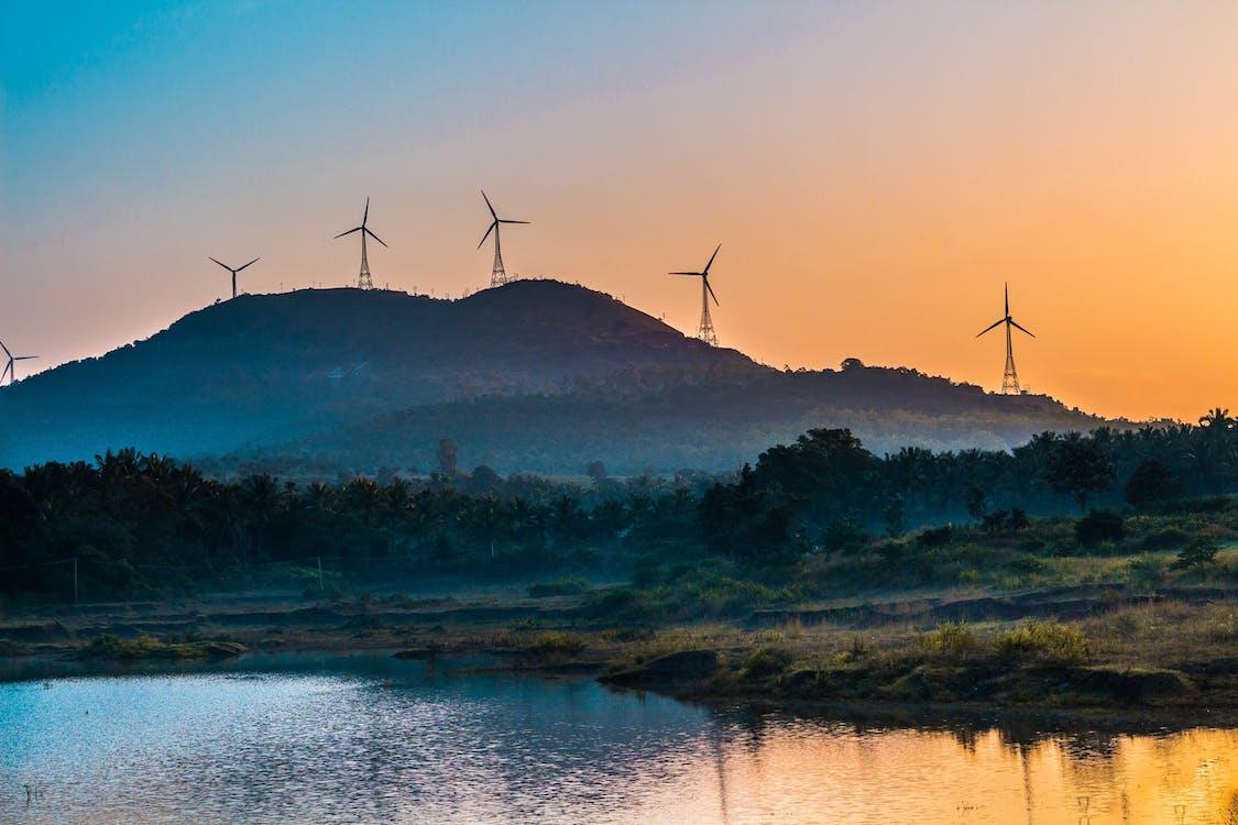 Windmills in Mountain Viewing Lake Under Orange Skies