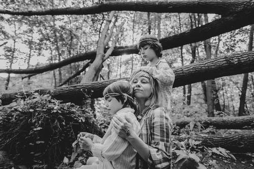 Grayscale Photography of Mother and Sons Beside Tree Log
