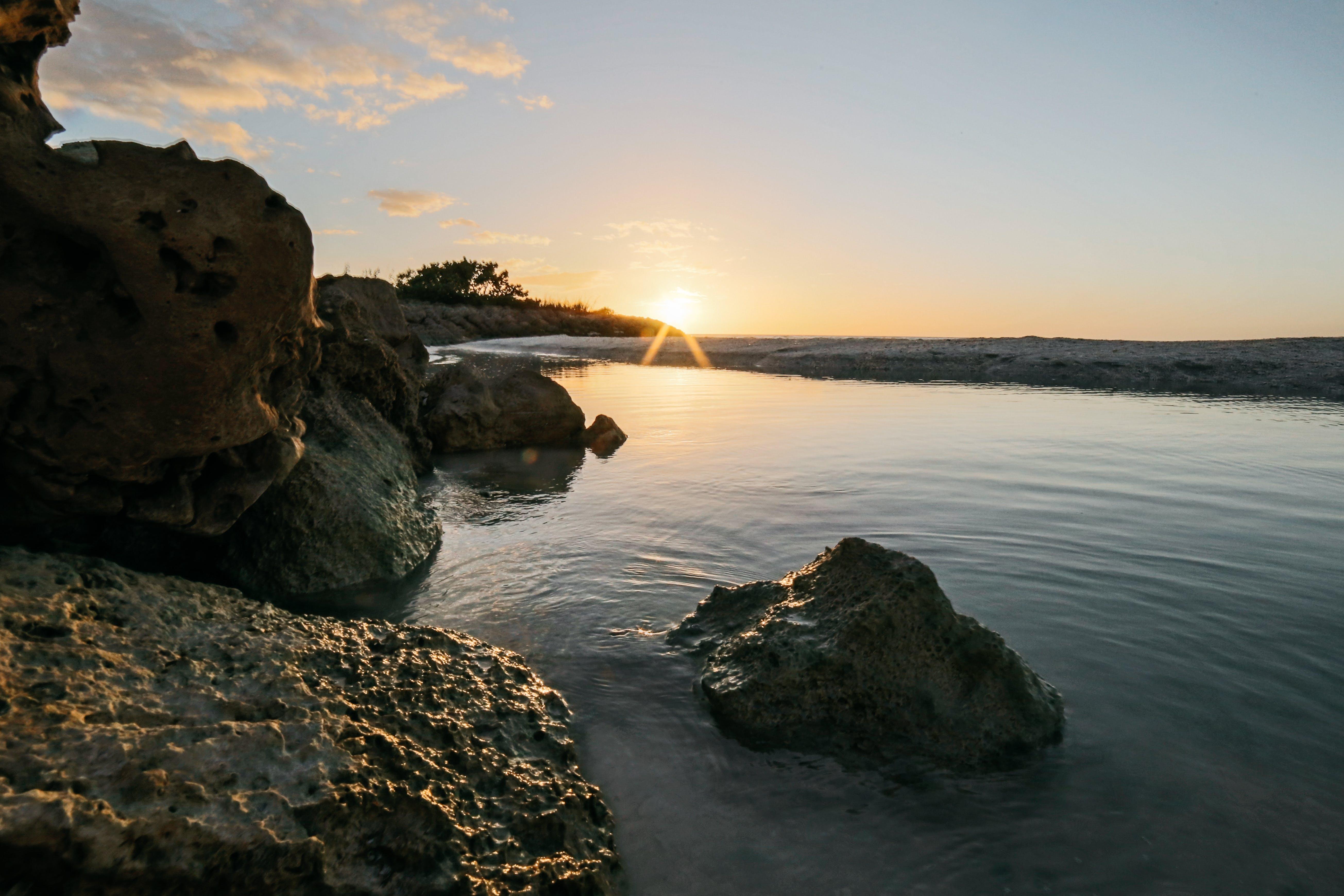 Безкоштовне стокове фото на тему «валуни, вода, дерево, Захід сонця»