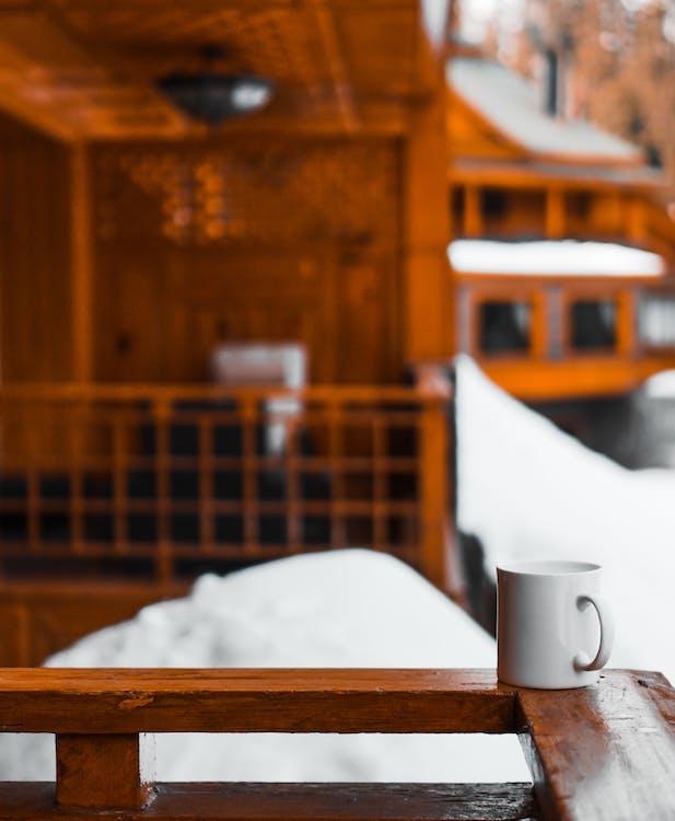 冬季,棕色木欄杆上的白色杯子的選擇性焦點照片