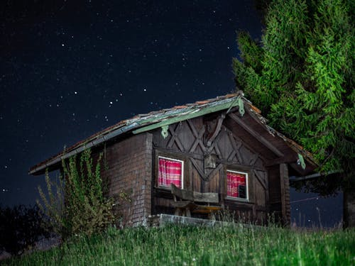 Wooden Cabin Near Trees at Night