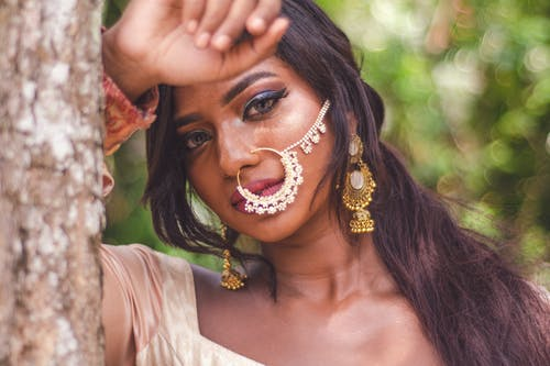 Selective Focus Close-up Portrait Photo of Indian Woman With Nose Ring Posing By Tree