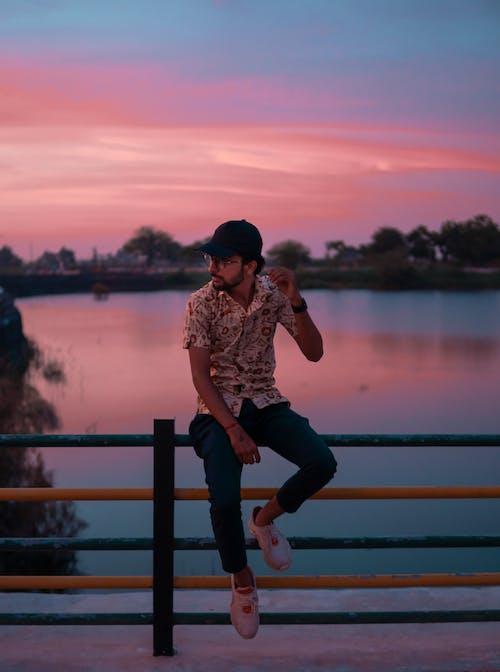 Photo Of Man Sitting On Fence