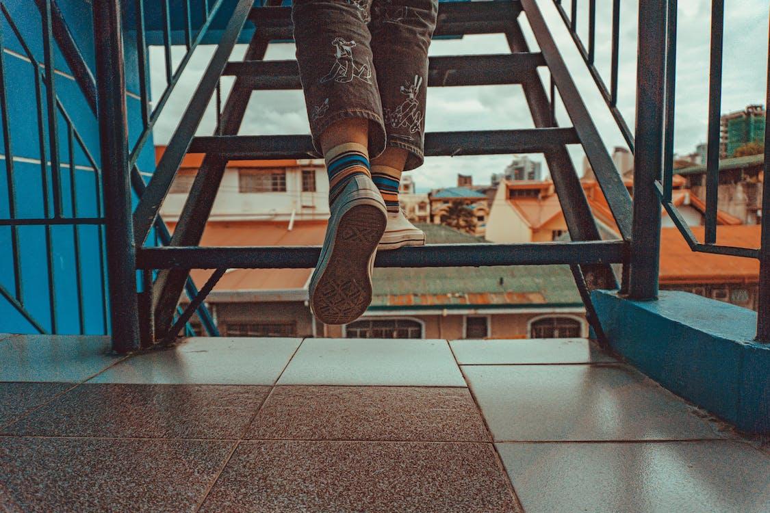 Person Wearing Rainbow Socks While Walking Upstairs