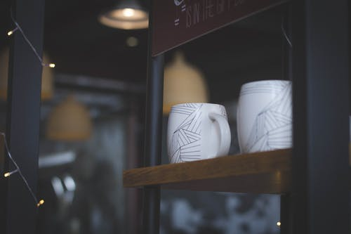 Two White Ceramic Cups on Shelf