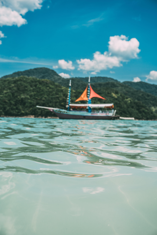 Black and Orange Boat Near Green Island