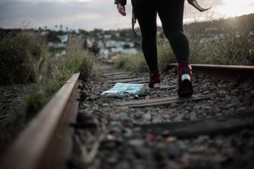 Photo of Person Walking on Train Track