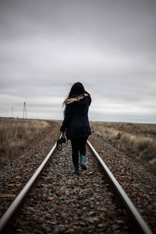 Woman Walking in Middle of Railway