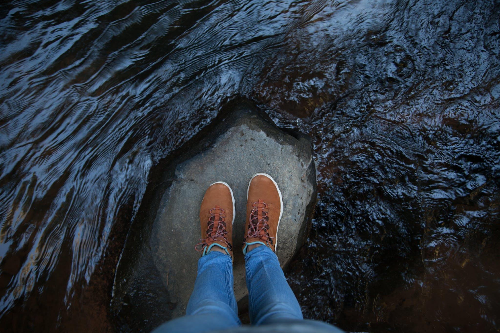 Person Standing on Rock in Between Running Water