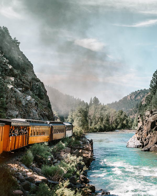Yellow and Multicolored Train Near Body of Water