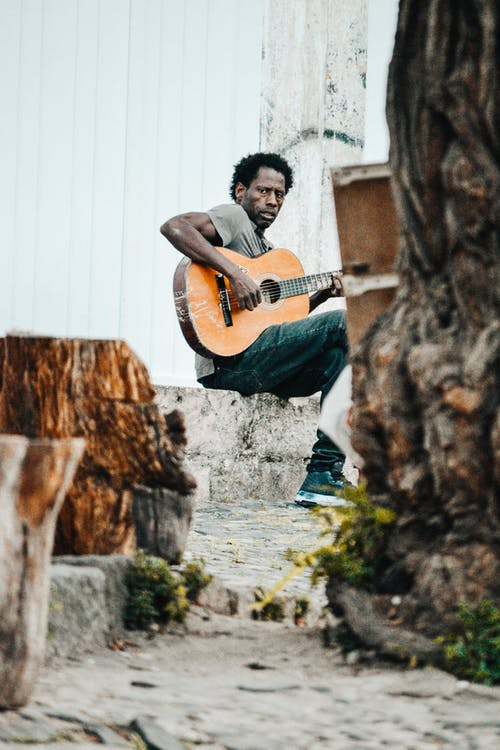 Photo of a Man Sitting on a Stone Playing Guitar