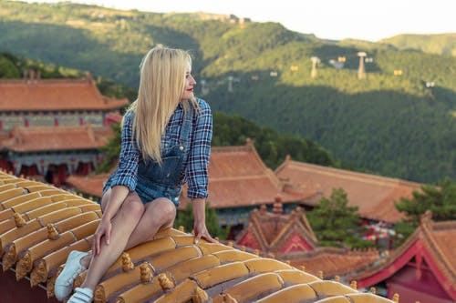 Photo of Smiling Woman Sitting on Top of Roof Looking Into the Distance