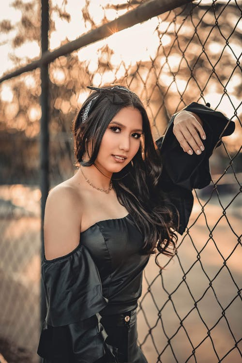 Photo of Woman in Black Outfit Leaning on Chain-link Fence Posing