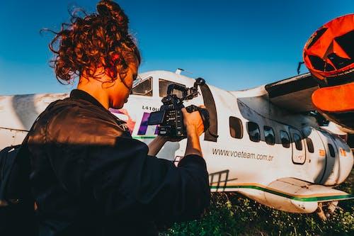 Foto d'estoc gratuïta de a l'aire lliure, avió, cabells llargs, càmera