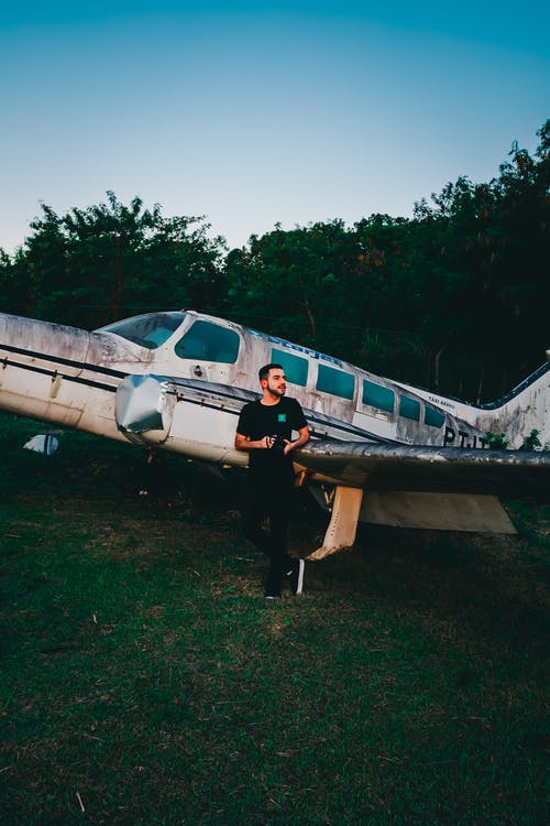 Photo of Man Standing Near Old Airplane