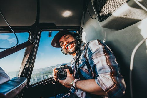Smiling Man Holding Dslr Camera Inside a Plane