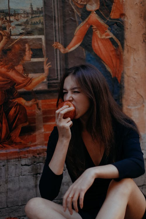 Photo Of Woman Eating Red Apple