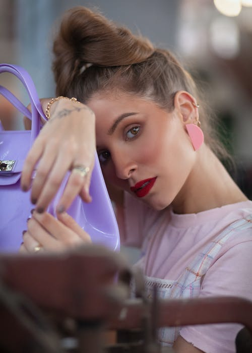 Close-up Photo of Woman in Pink T-shirt Posing By Purple Bag