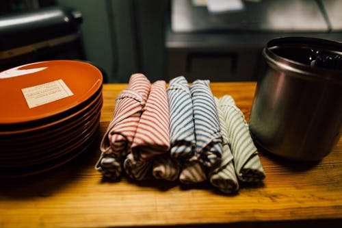 Rolled Assorted-colored Hand Towels Near Round Orange Ceramic Plates on Wooden Table