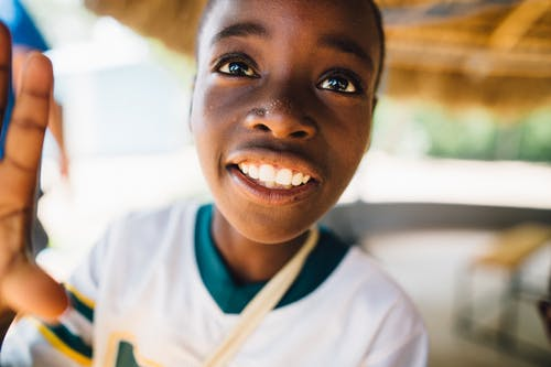 Child Wearing White and Green V-neck T-shirt Grinning