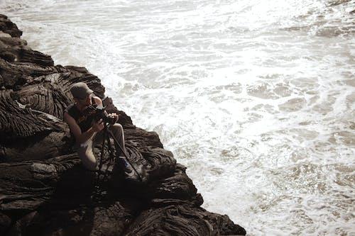Person Assembling Camera Stand Near Shore