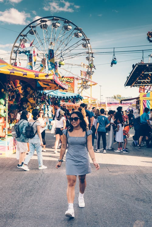 Woman in Gray Square-neck Mini Dress and White Sneakers Walking on Street With Ferris Wheel Background