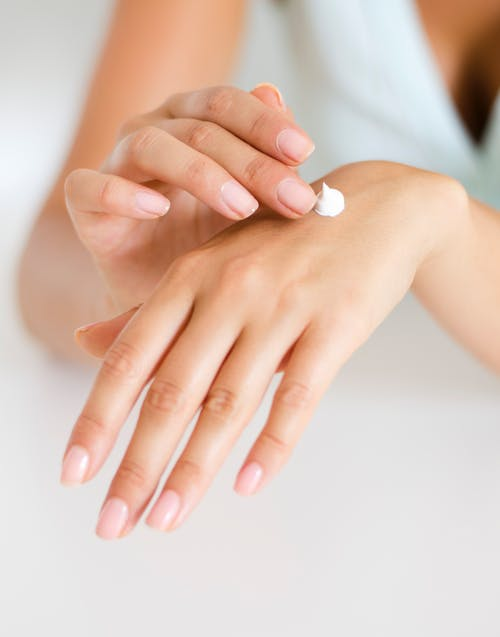 Woman Applying Lotion on Hand