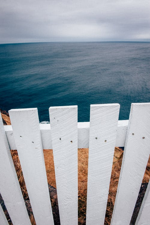 White Wooden Fence Beside Body of Water