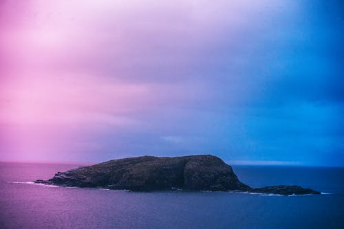Green Island Under Blue and Pink Skies