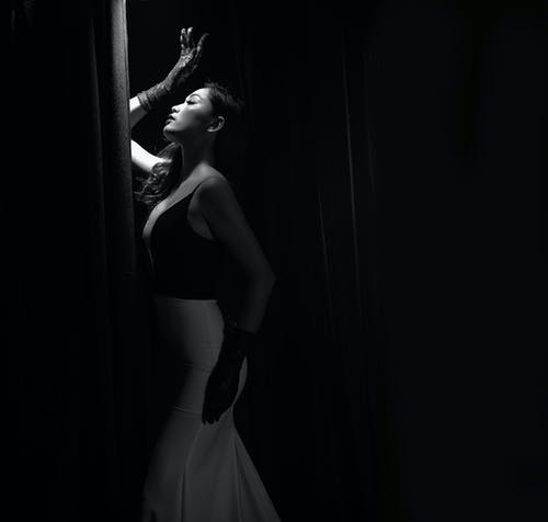 Side View Grayscale Photo of Woman in Glamorous Dress Posing With Her Eyes Closed By Curtain