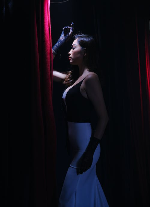 Side View  Photo of Woman in Glamorous Dress Posing With Her Eyes Closed By Curtain