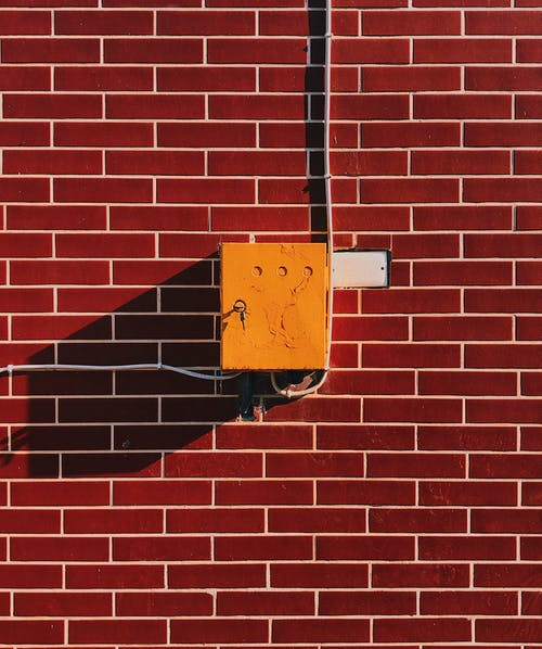 Yellow Electric Box on Brown Brick Wall