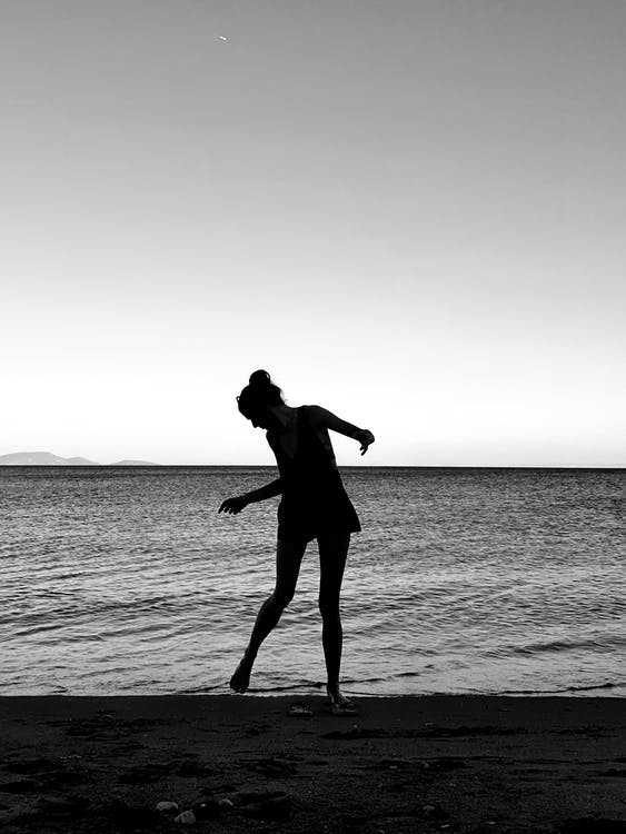 Grayscale Photo of Woman Standing on Shore Looking at Her Feet